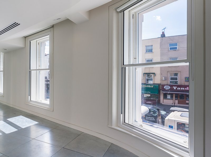 Vertical sliding secondary glazing with minimal frames to blend into the original frames
