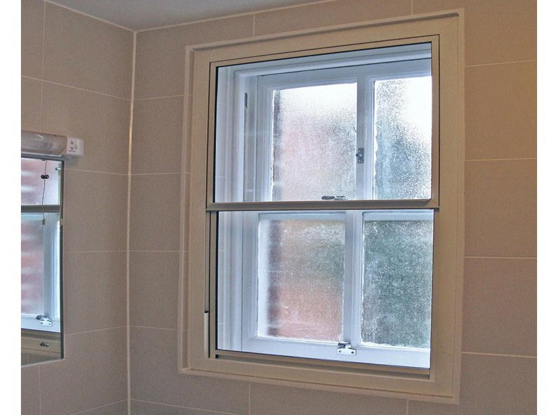 Vertical sliding secondary glazing in Shooters Hill Police Station bathroom